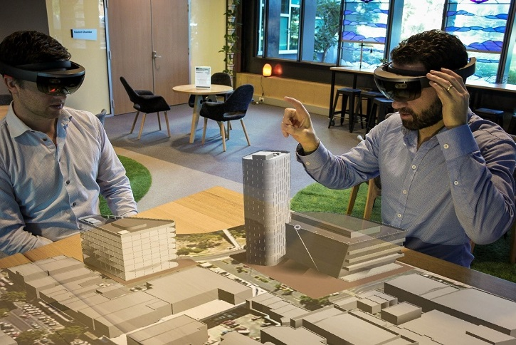 Two men wearing HoloLenses gazing at 3D VR model of Werribee City Centre